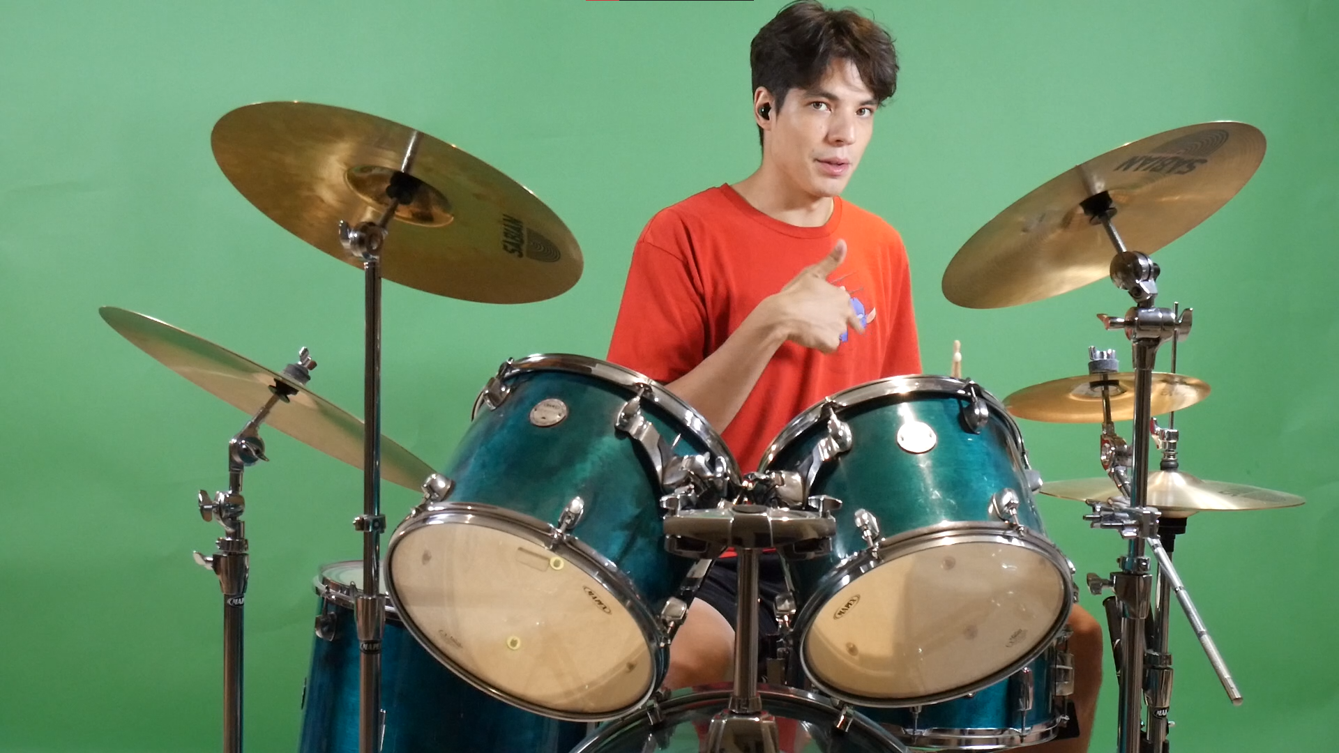 A picture of Nicolas Merlo in an orange t-shirt, sitting at a drum set