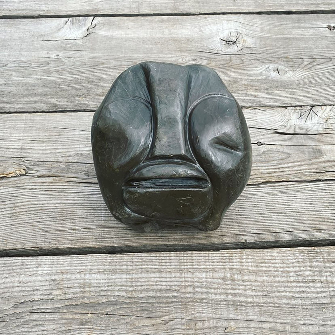 A natural hand carved stone resembling a human face, with an exaggerated nose and lips. The stone has been sanded to be smooth to the touch and burnished with olive oil to bring the true color out from the stone. (Black)