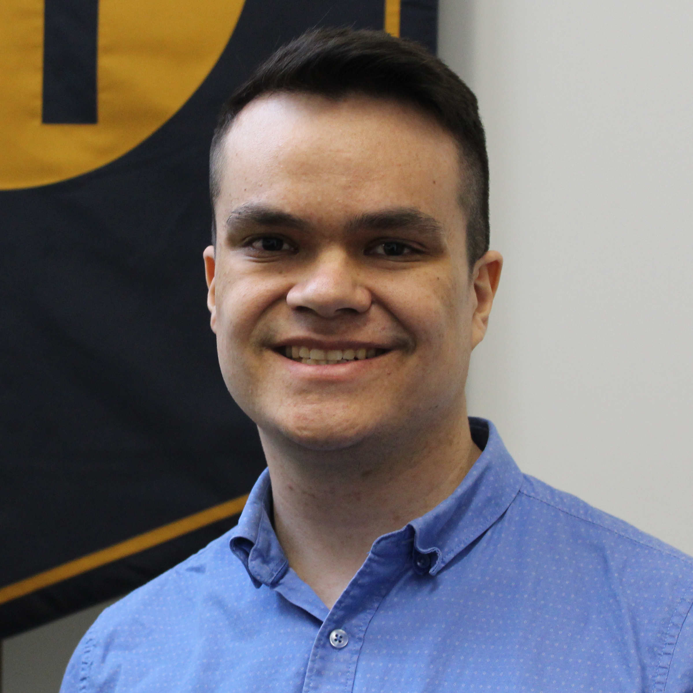 A headshot of Joshua Wood. They are wearing a blue button-up shirt. They are in front of a school banner which is hanging on the wall behind them.