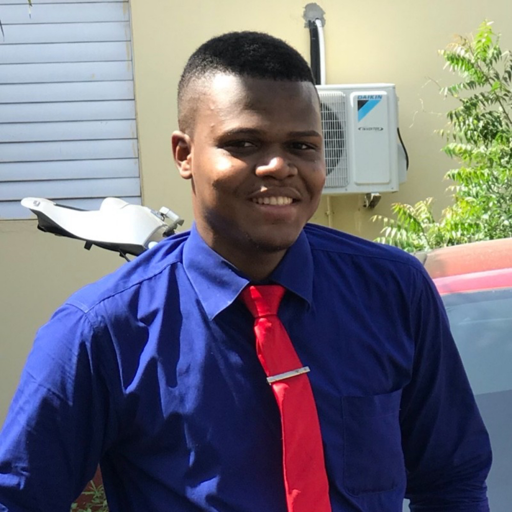 Picture of Stephaun outdoors, wearing a blue shirt with a red tie