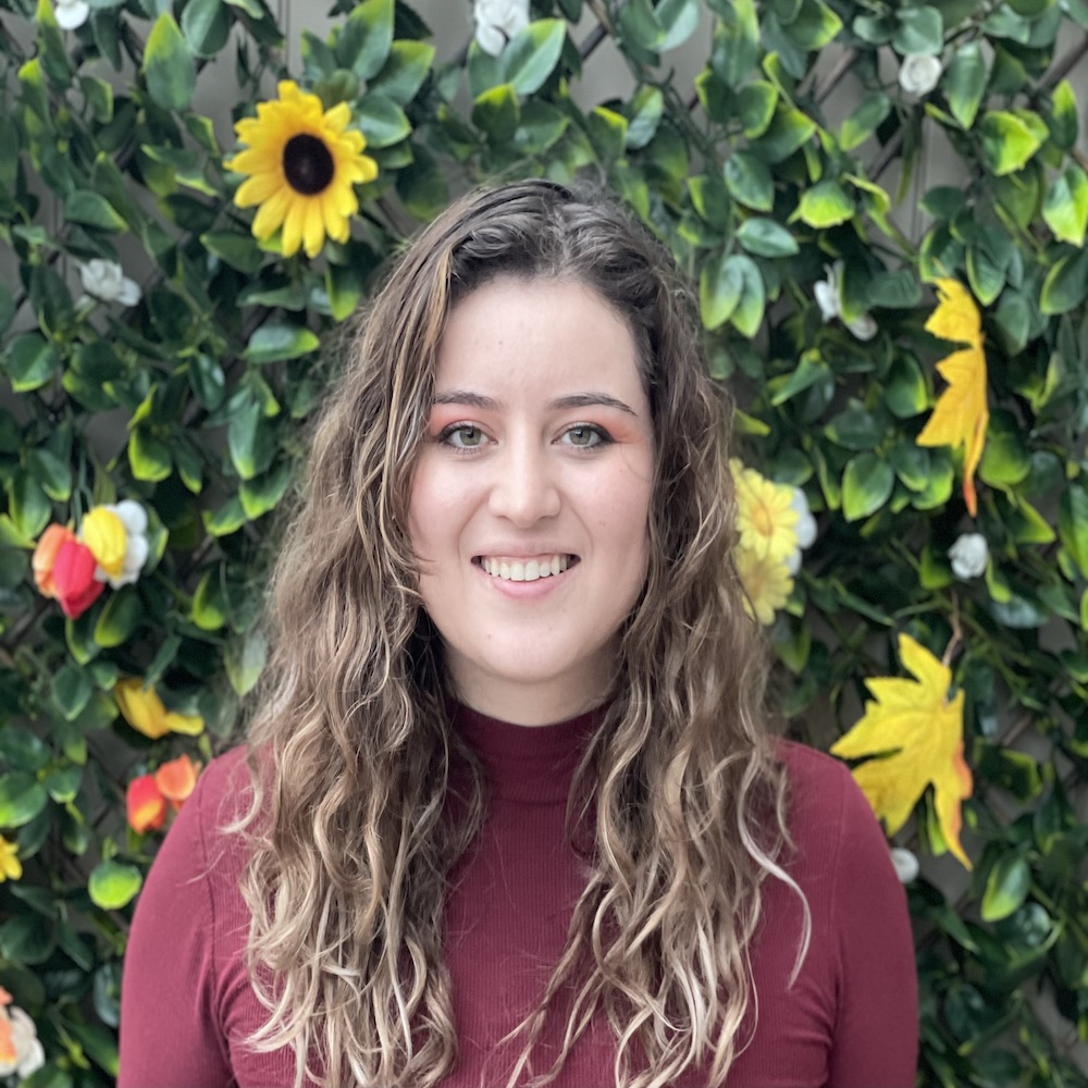 Picture of Vanessa, outdoors with flowers behind her, wearing a red turtle neck shirt