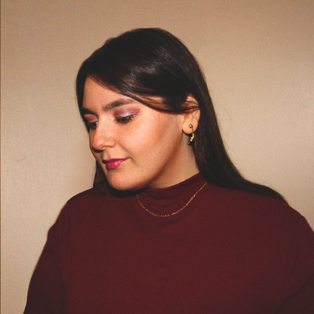 Vall Fierro, a woman with long brown hair in 3/4 view looking down to the left wearing a burgundy turtleneck