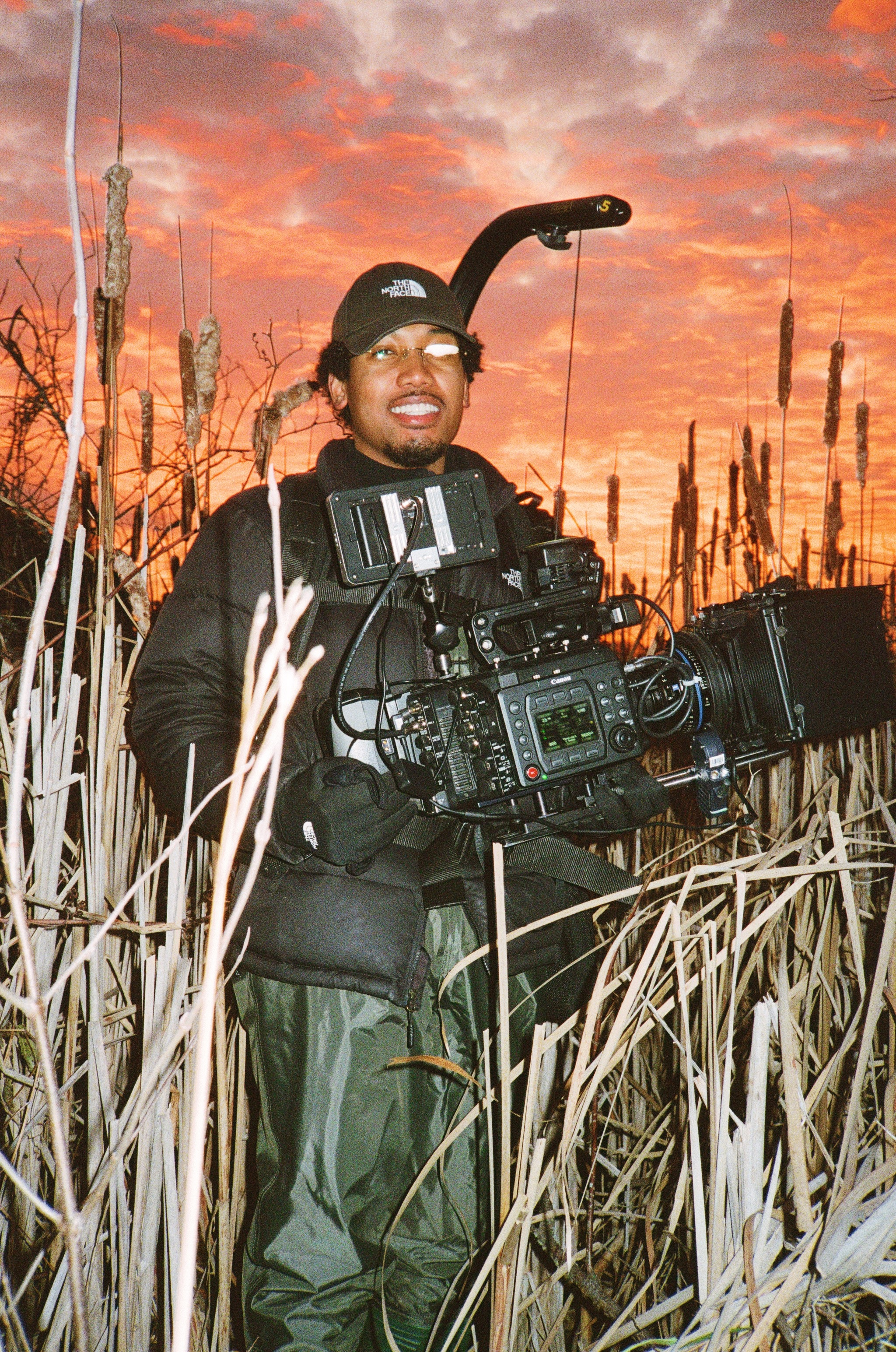 FMTV student Joel Mens, standing in a marsh wearing waders and a Steadicam rig.