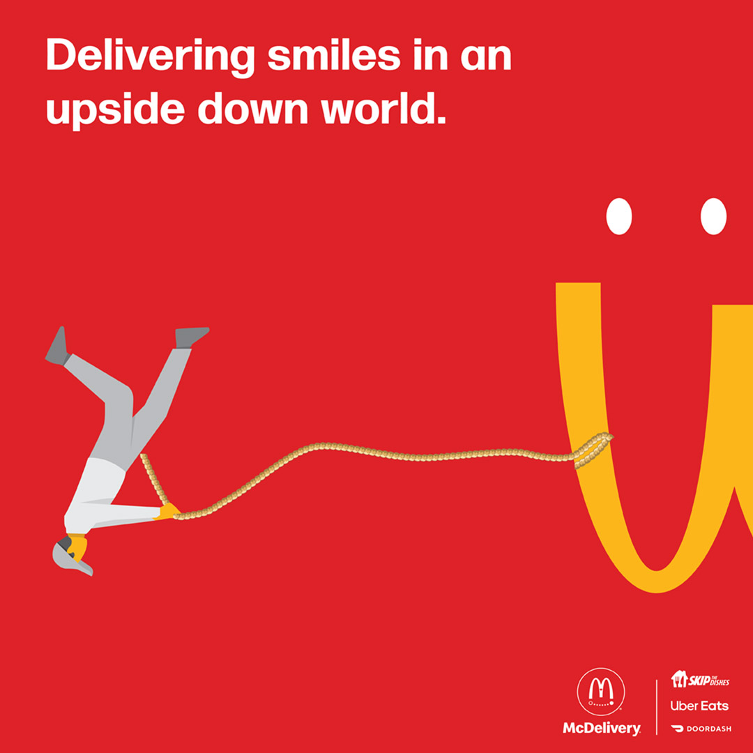 """A McDonalds ad shows a red background with upside down golden arches. A drawing of a small figure pulls the arches with a rope. Two dots above the arches resmble eyes. In white type at top it says """"Delivering smiles in an upside down world."""" The McDelivery logo, Skip the Dishes, UberEats and Doordash logos in white at the bottom right corner."""