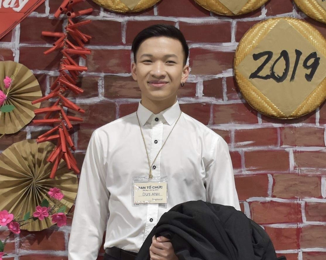 Picture of Anh, smiling to the camera and wearing a white shirt while holding a jacket.