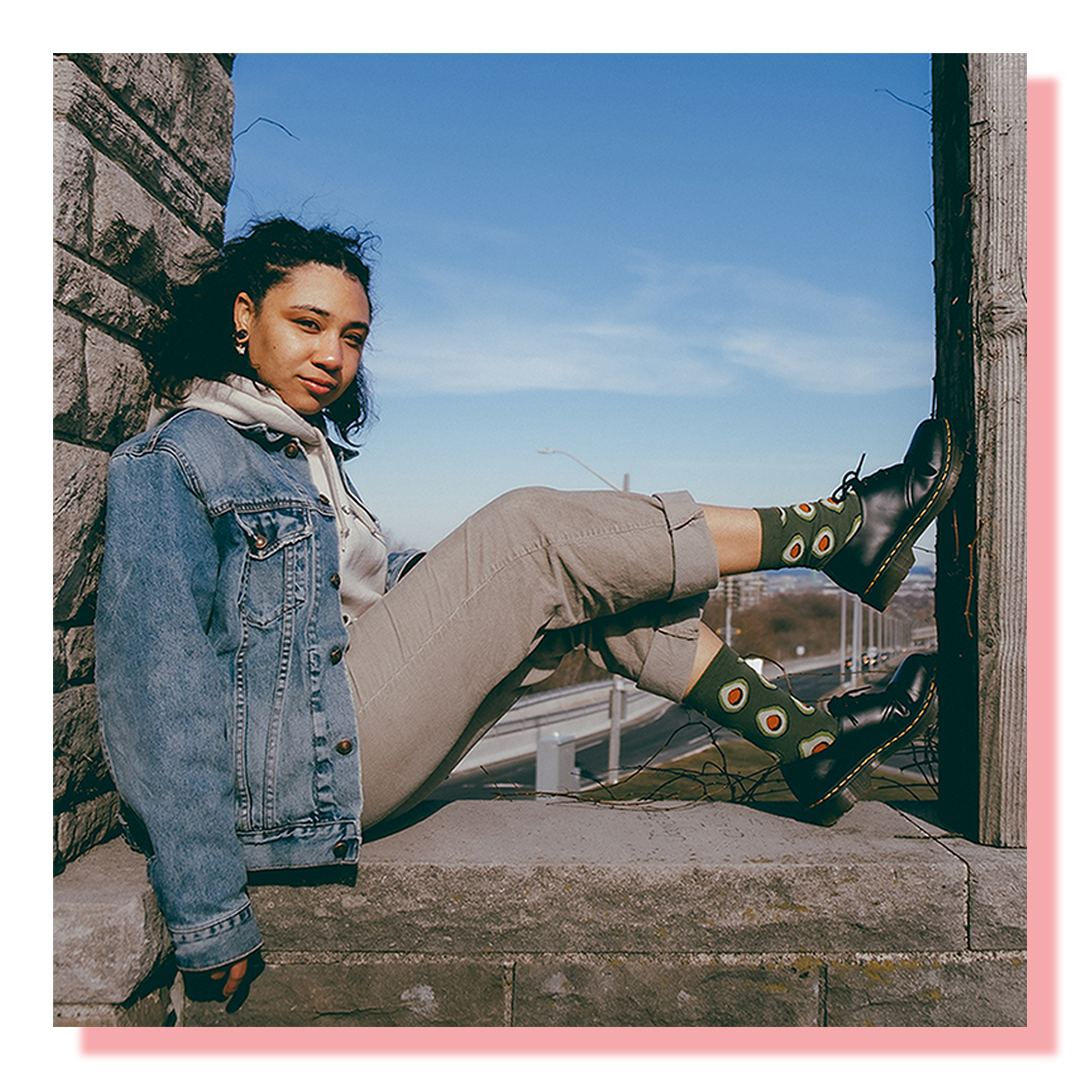 A model wearing avocado socks sitting with in a small enclosure with her feet propped up on the wall
