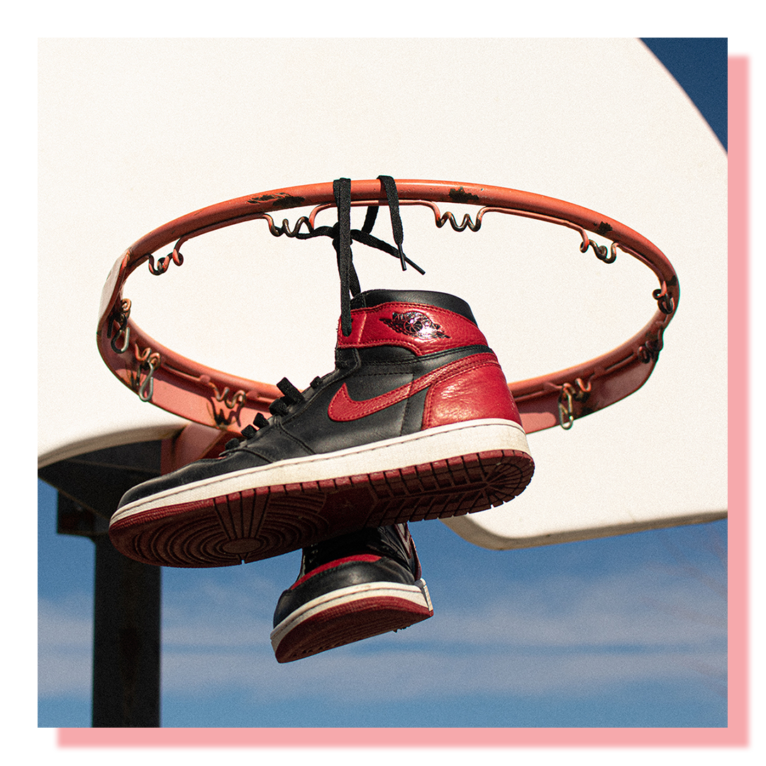 Sneakers, black and red, tied together and hung up on the rim of a basketball net.