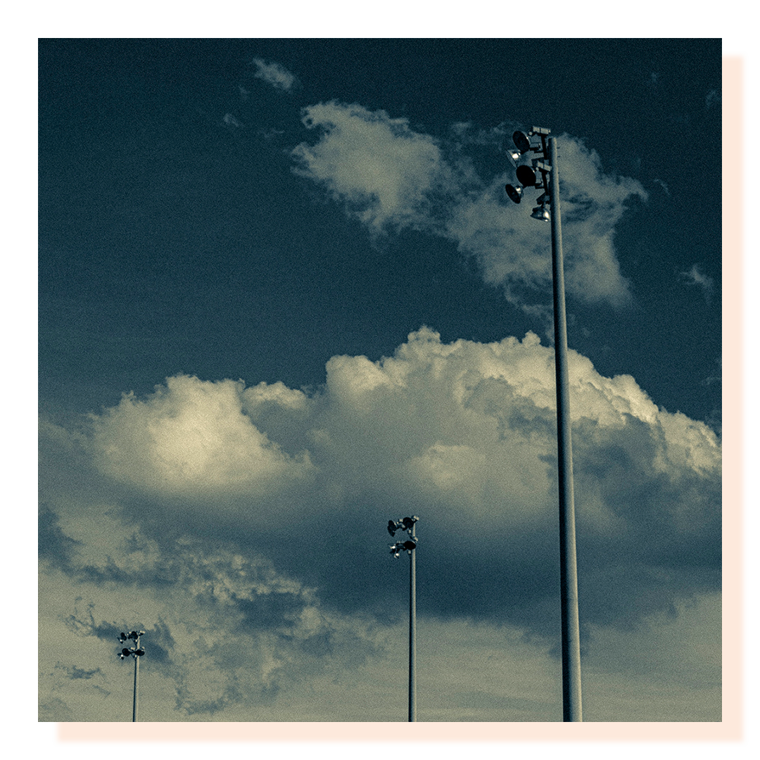 Exterior lamp posts shot looking up and framed against a cloudy sky backdrop.