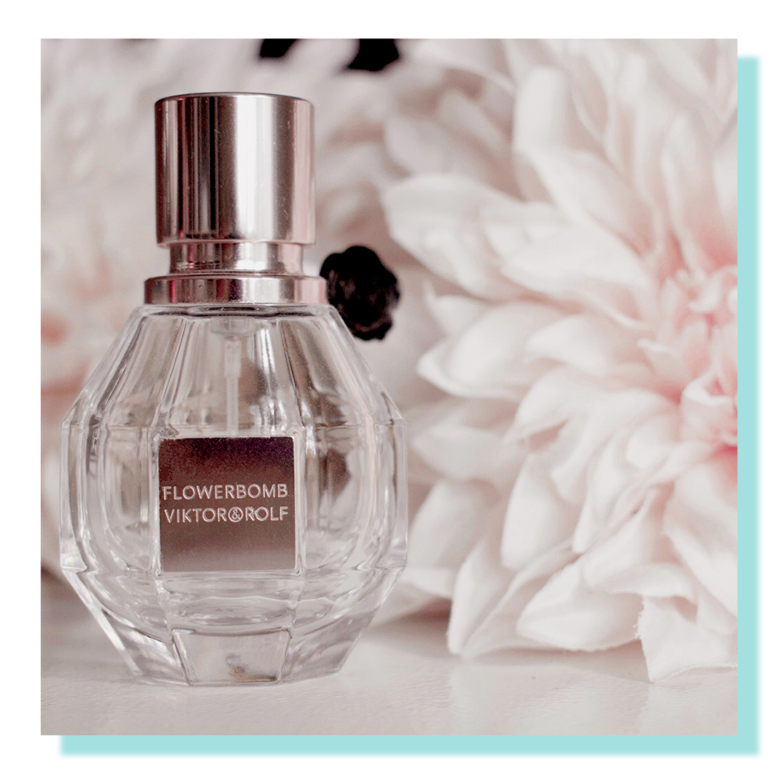 Small clear bottle with soft pink flowers behind