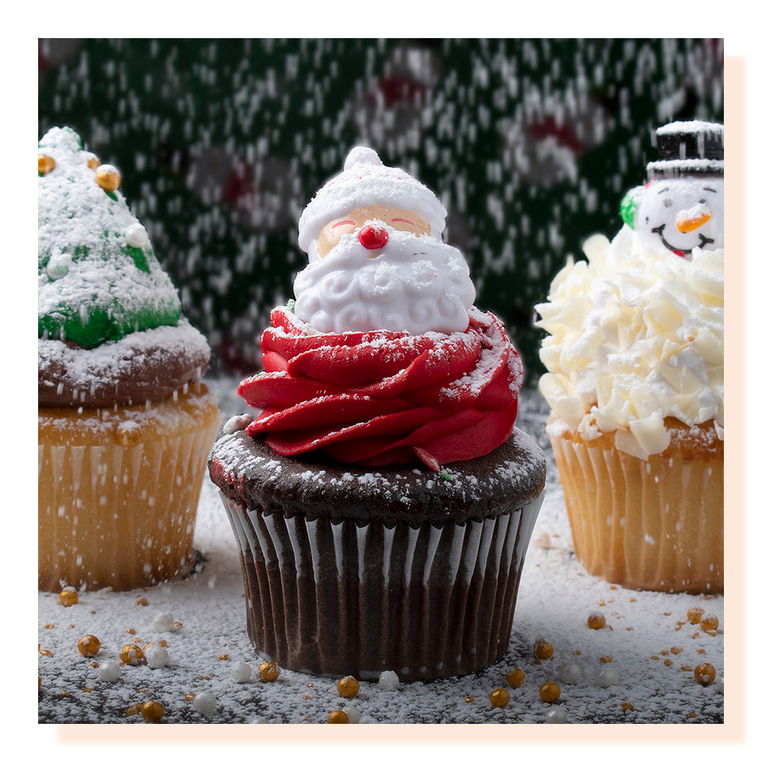 Three cupcakes with santa and Christmas holiday decorations. Sugar snow is falling on cupcakes.