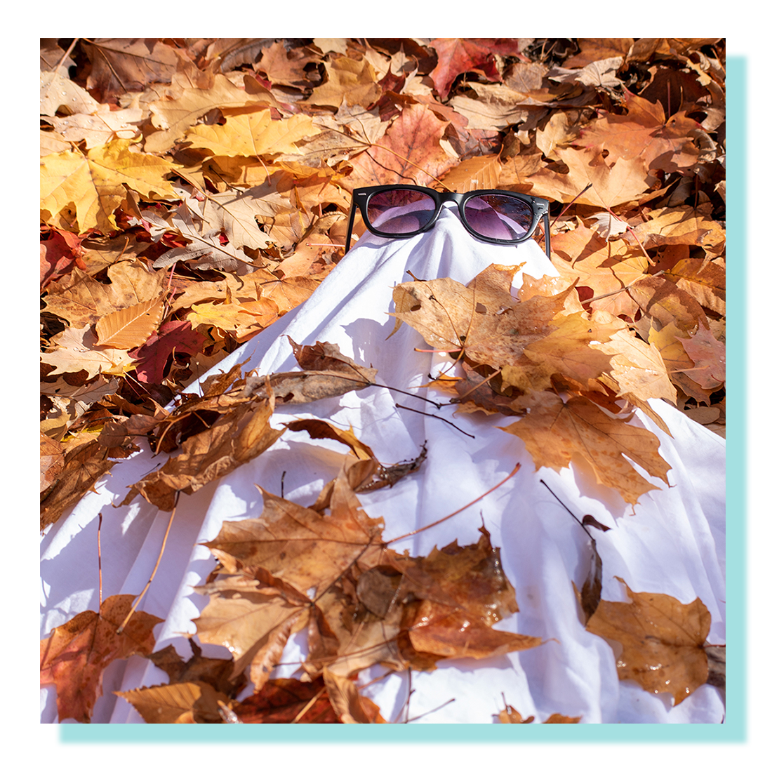A person in a dressed as a ghost wearing glasses and lying on a bed of leaves.