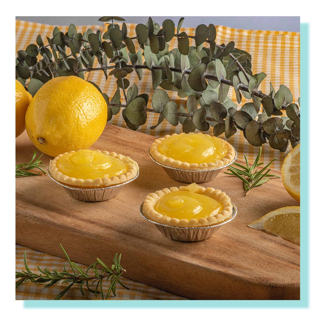 Lemon Tarts displayed on a wooden board and gingham tablecloth and decorated with lemon wedges and eucalyptus.