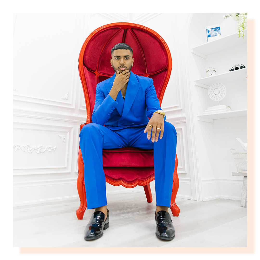 A man wearing a bright blue suit sitting on large royal-looking bright red chair. Man's face in hands.