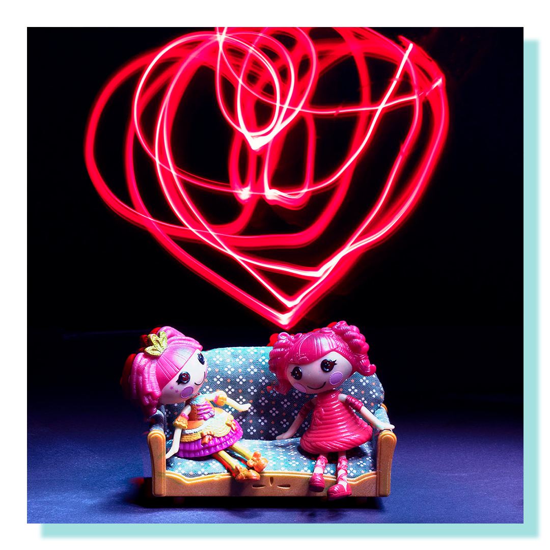 Two small toy dolls sitting on a dollhouse sofa with a red heart light in the background.