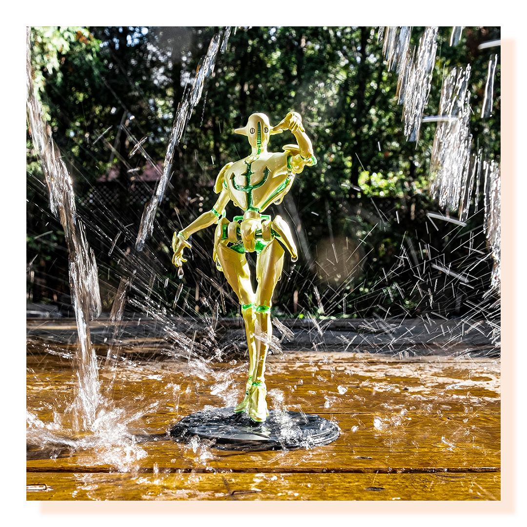 Statue in water posing while water is falling around it.