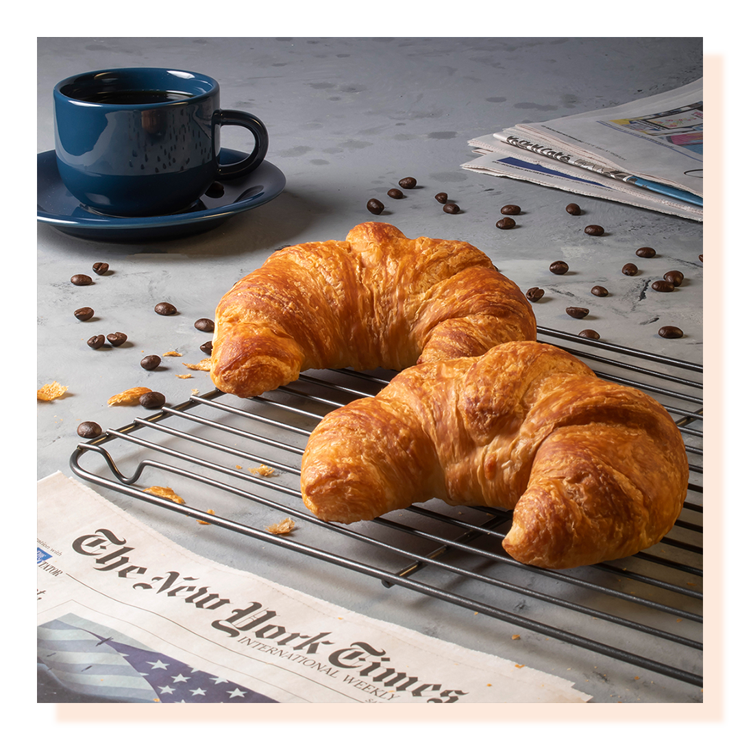 Croissants cooling on a rack with the New York Times and a cup of coffee, coffee beans scattered around.