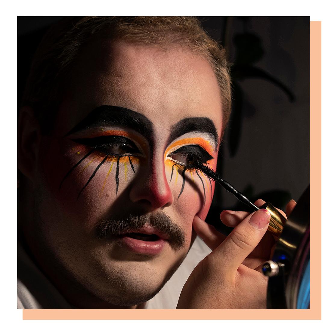 A close up shot of a man's face applying clown makeup.
