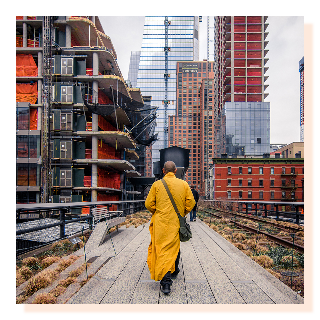 Man walking between two tall buildings wearing a yellow robe.