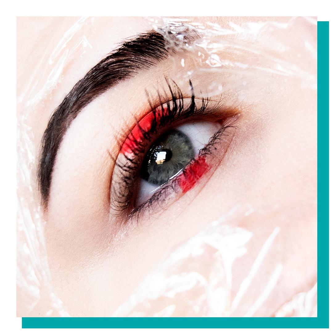 Close up of an eye with saran wrap and red makeup.