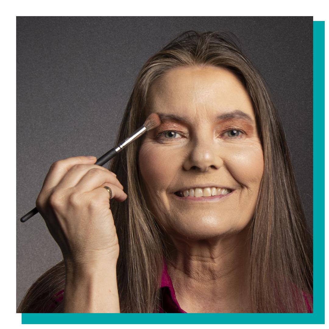 Woman holding makeup brush close to face.