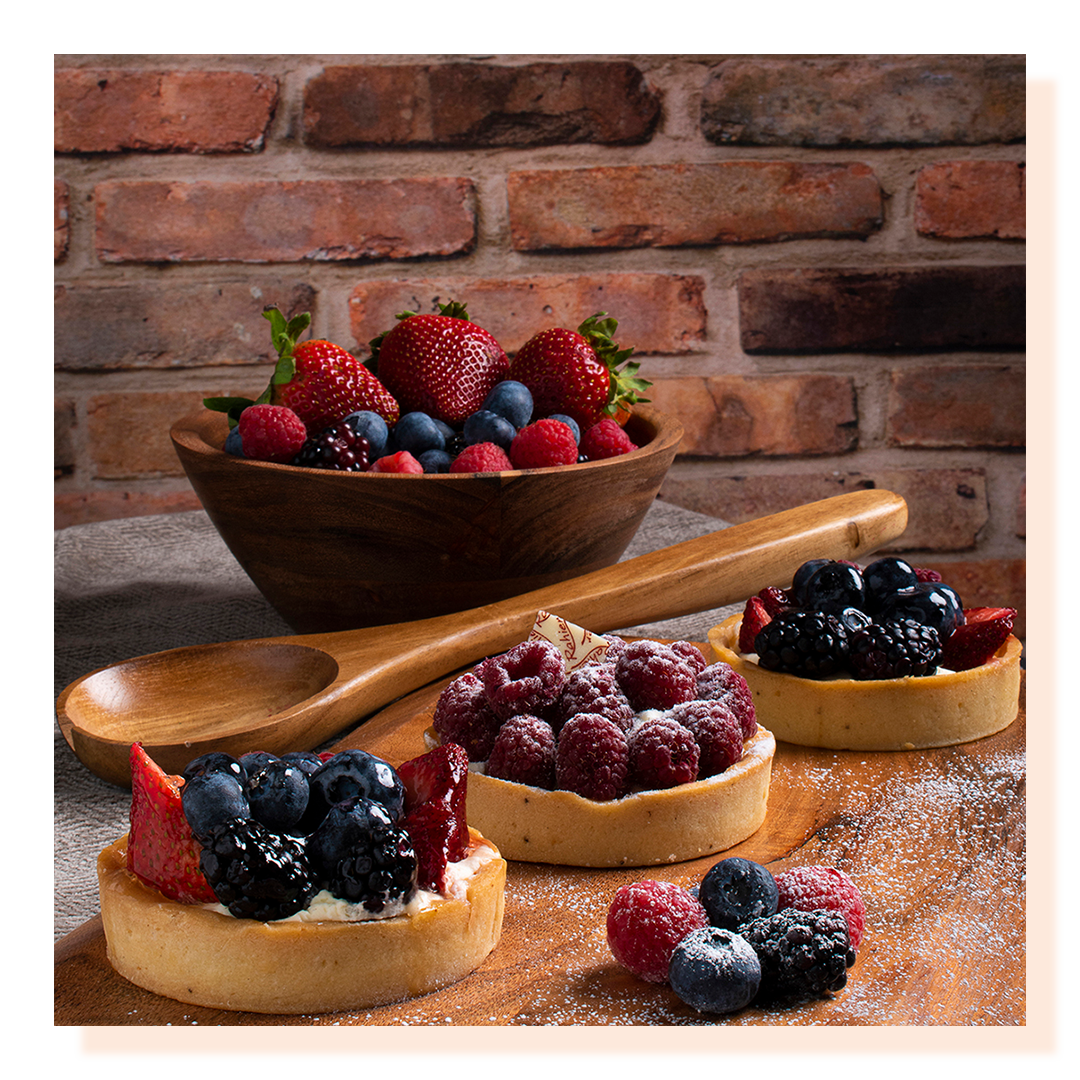 Berry tarts and berry bowl of fruit on a wooden chopping board and brick wall in the background.