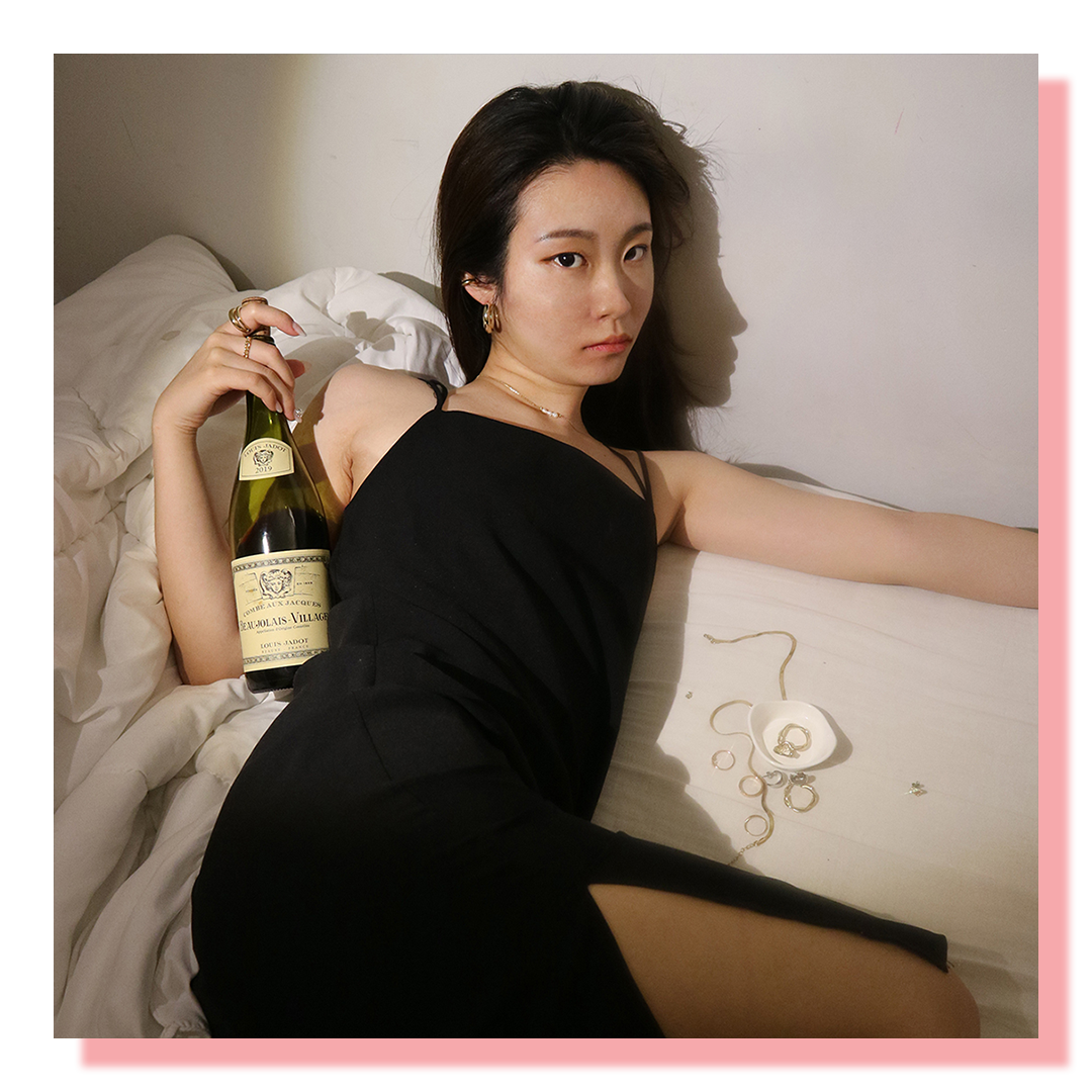 Woman with black dress lying on bed holding a wine bottle and looking at camera.