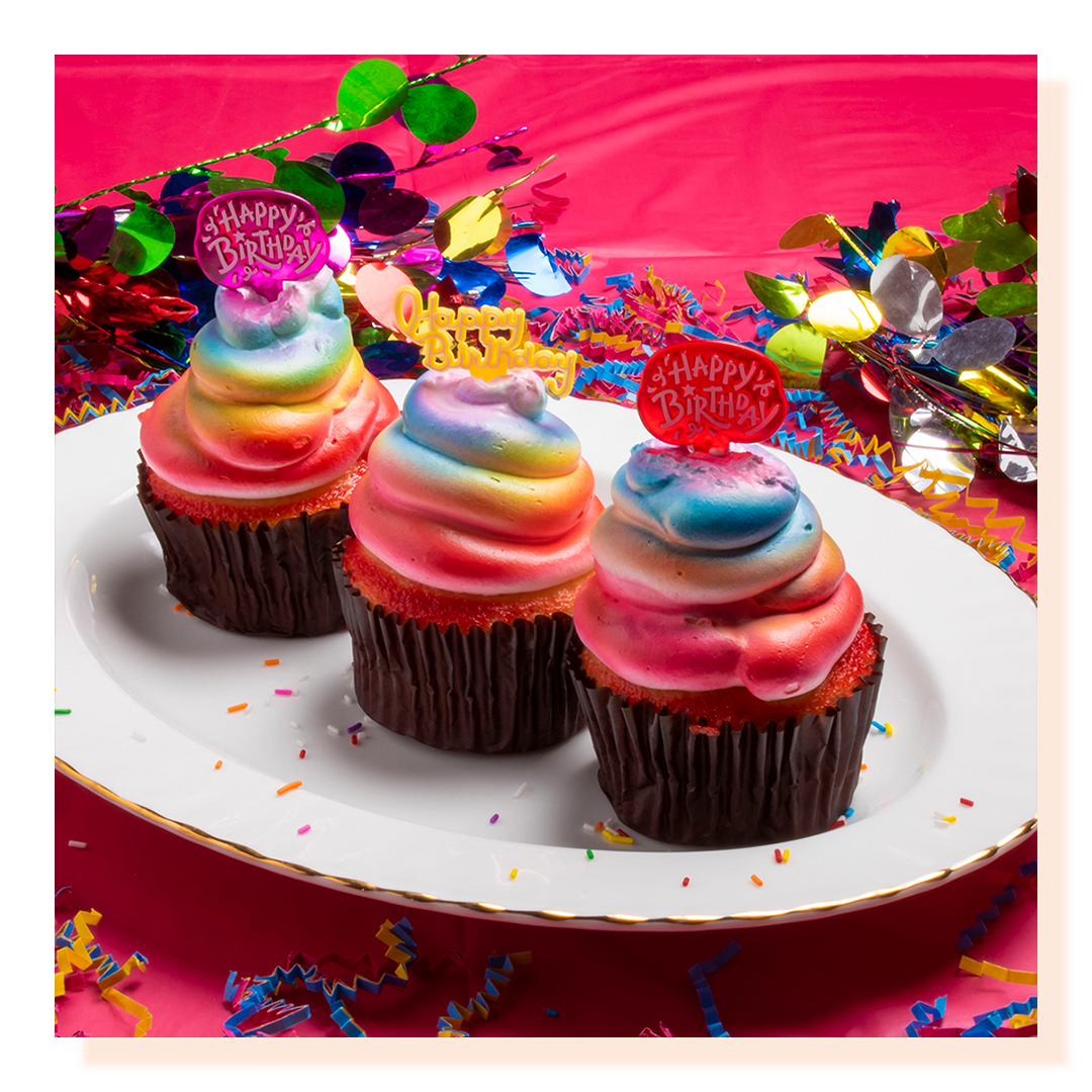 Three multi-coloured cupcakes on a white plate