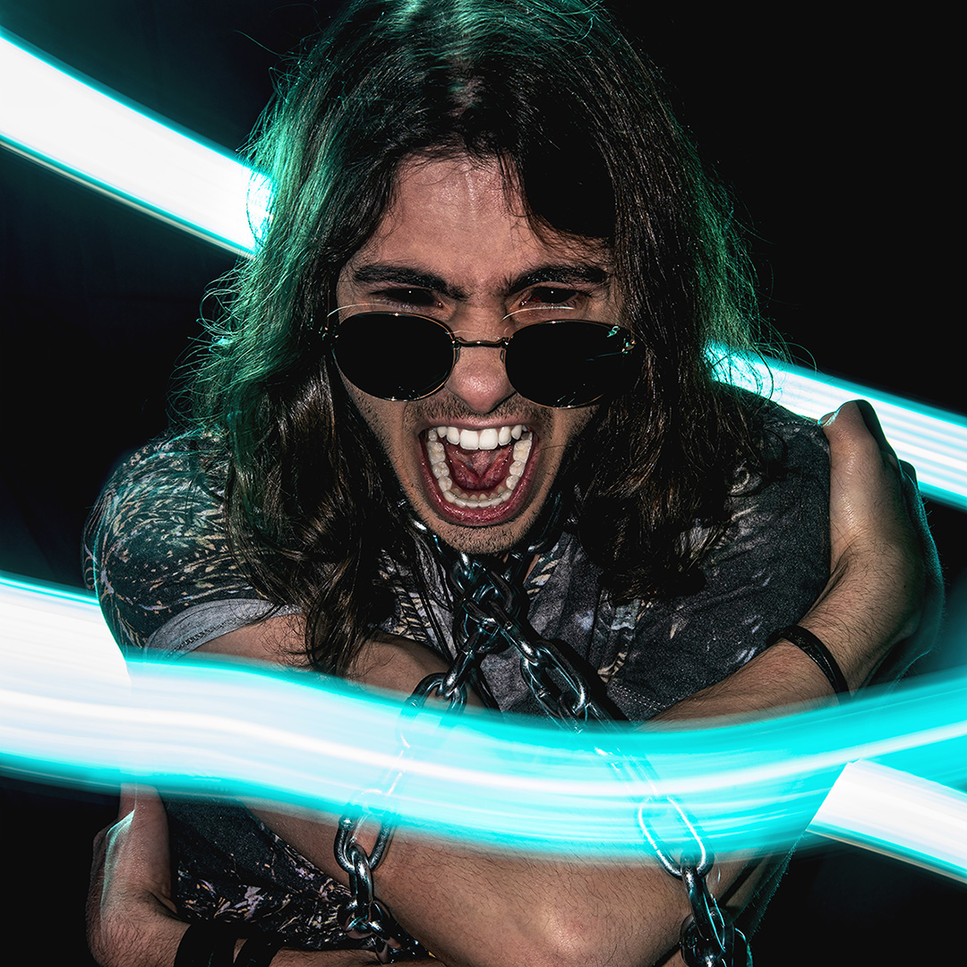The photo shows a man with long dark hair, screaming with mouth open facing the camera. There is a curved strip of light blue light circling him, and he has chains around neck and arms