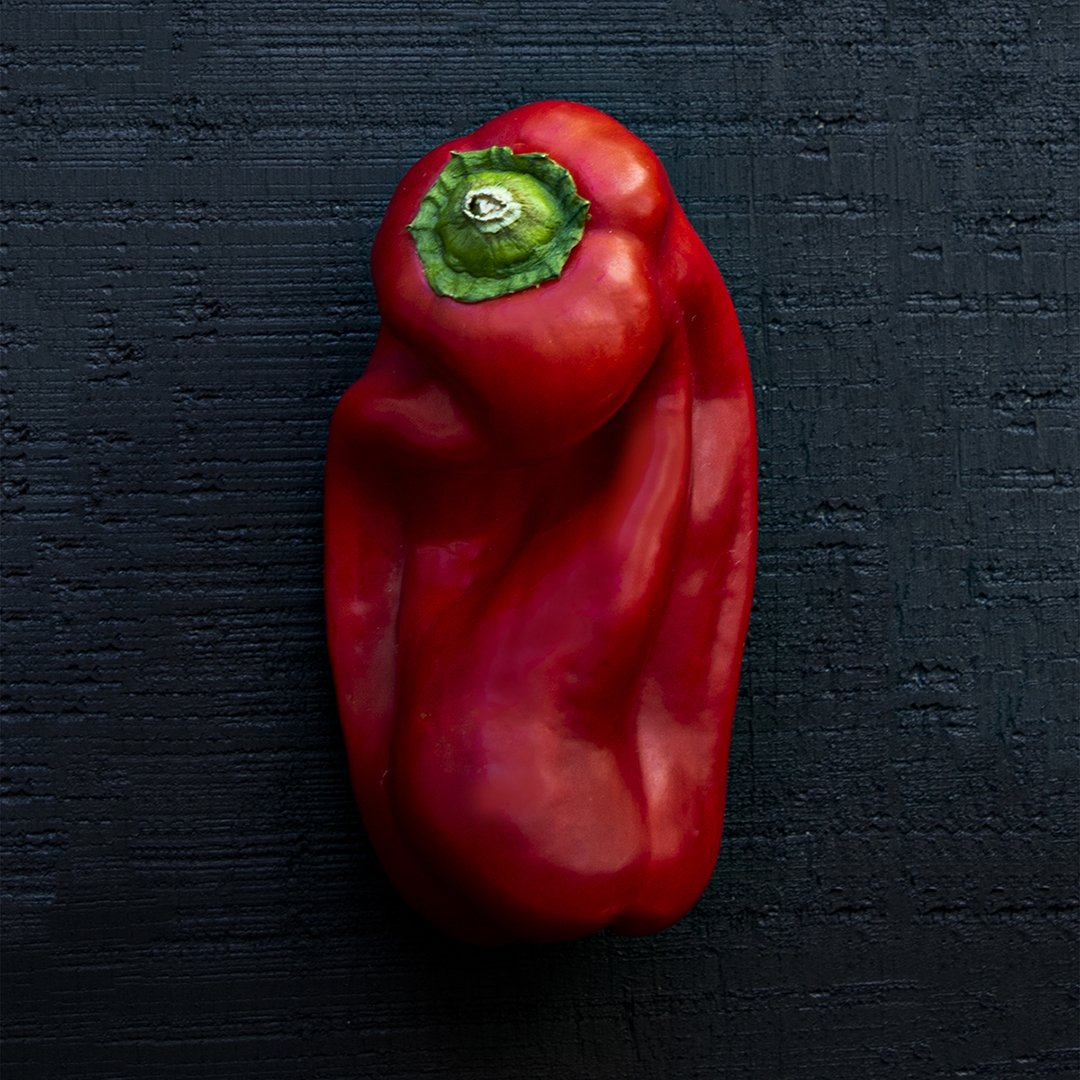 A red pepper, beets and eggplant, photographed individually on a dark background and shown in three photographs side by side
