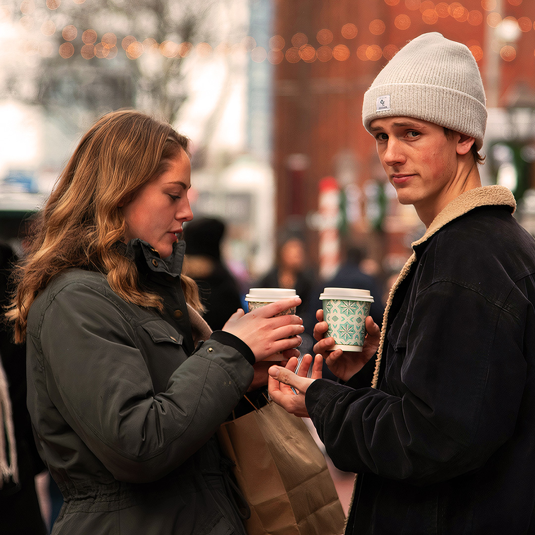 A couple standing in a café, boyfriend on right looking towards camera. Girlfriend on left looking down, passing cup of hot drink to boyfriend