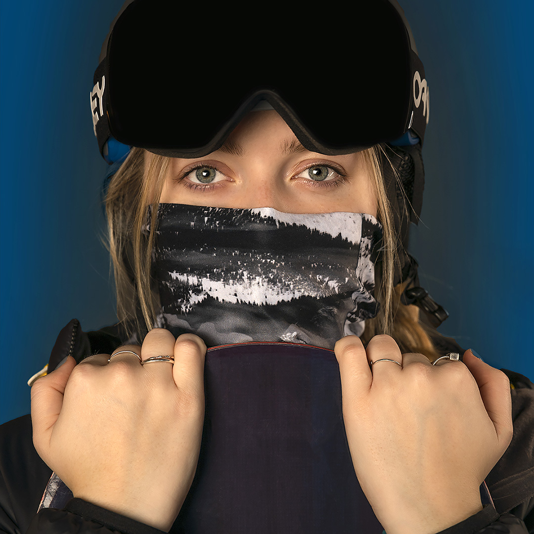 Headshot of a woman snow boarder, looking over the top of a snowboard. Wearing a mask over nose and mouth, with snow goggles on her forehead
