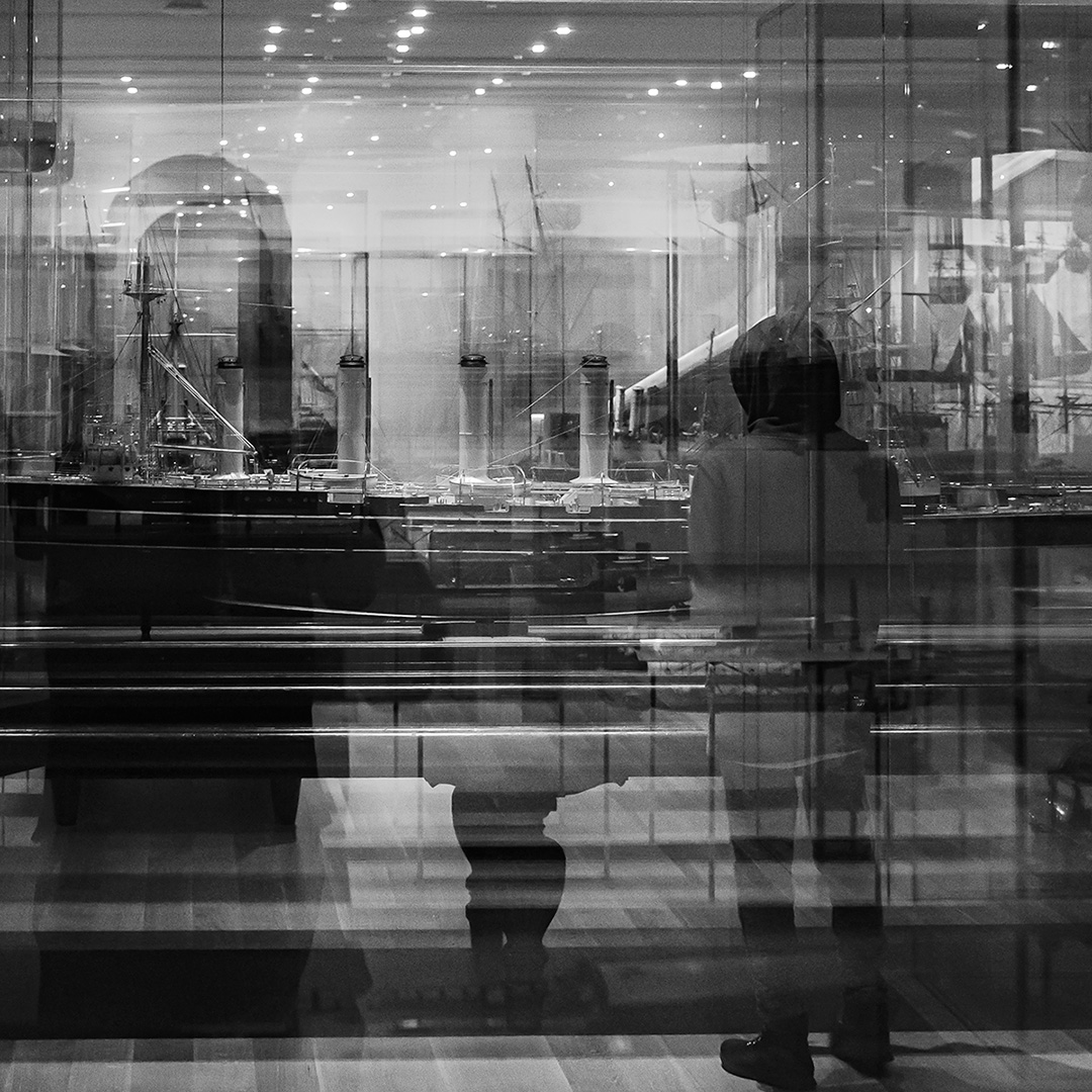 Male wearing hoodie standing with back to camera, looking at large model boats in glass showcases.