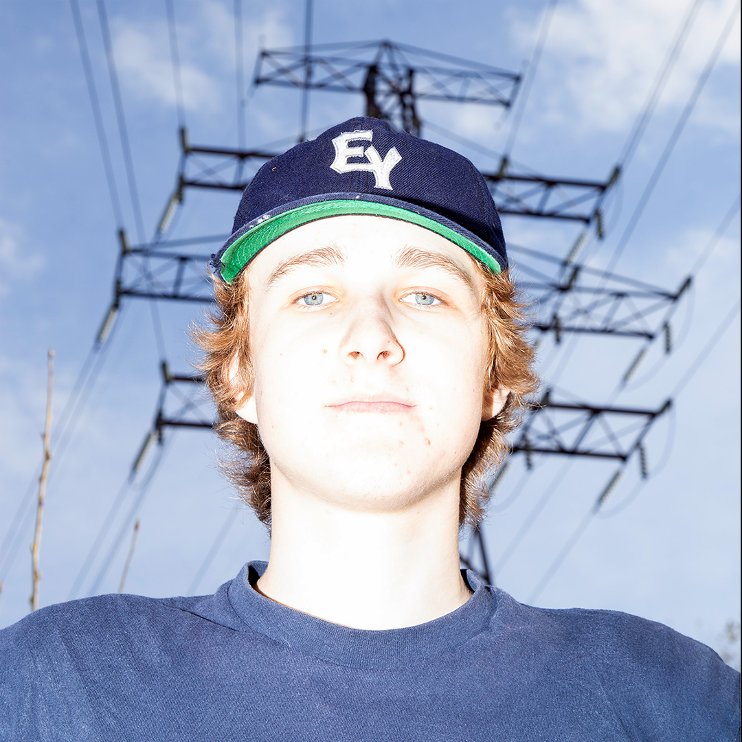 A young man gazing at the camera with a transmission tower in the back