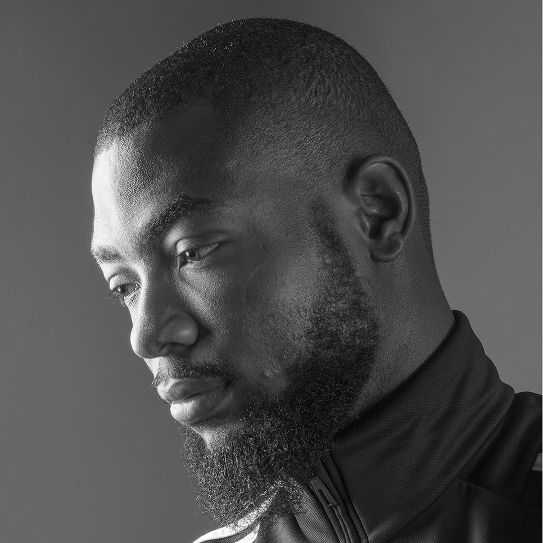 Black and white head shot profile of an athlete looking off to the side with his head tilted slightly downwards