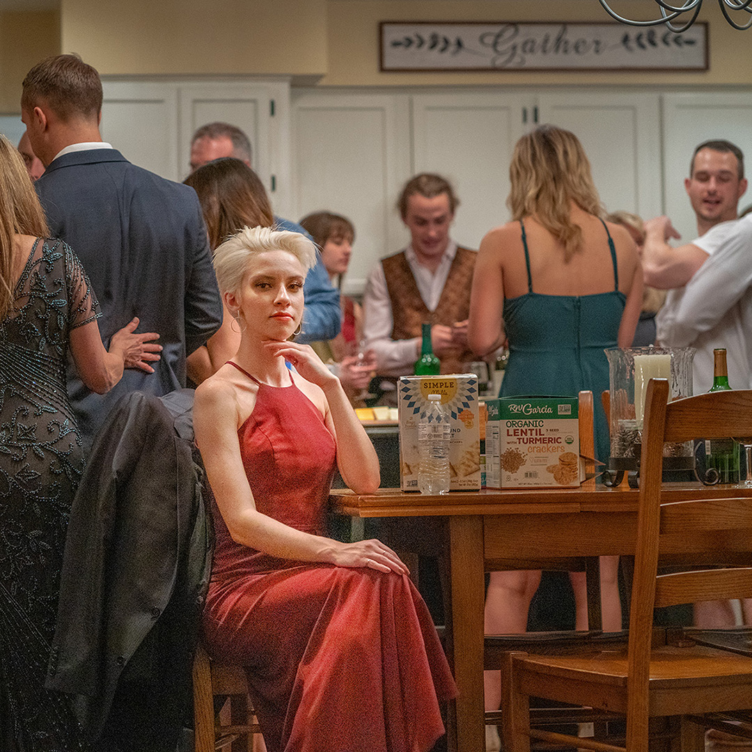 A blonde woman is sitting at a tabloe during a party with people standing around her in various unrelated conversations