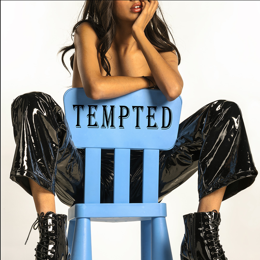 Woman wearing shiny black leather pants and leather platform boots straddles a plastic blue chair. Top half of her face is cropped out of shot
