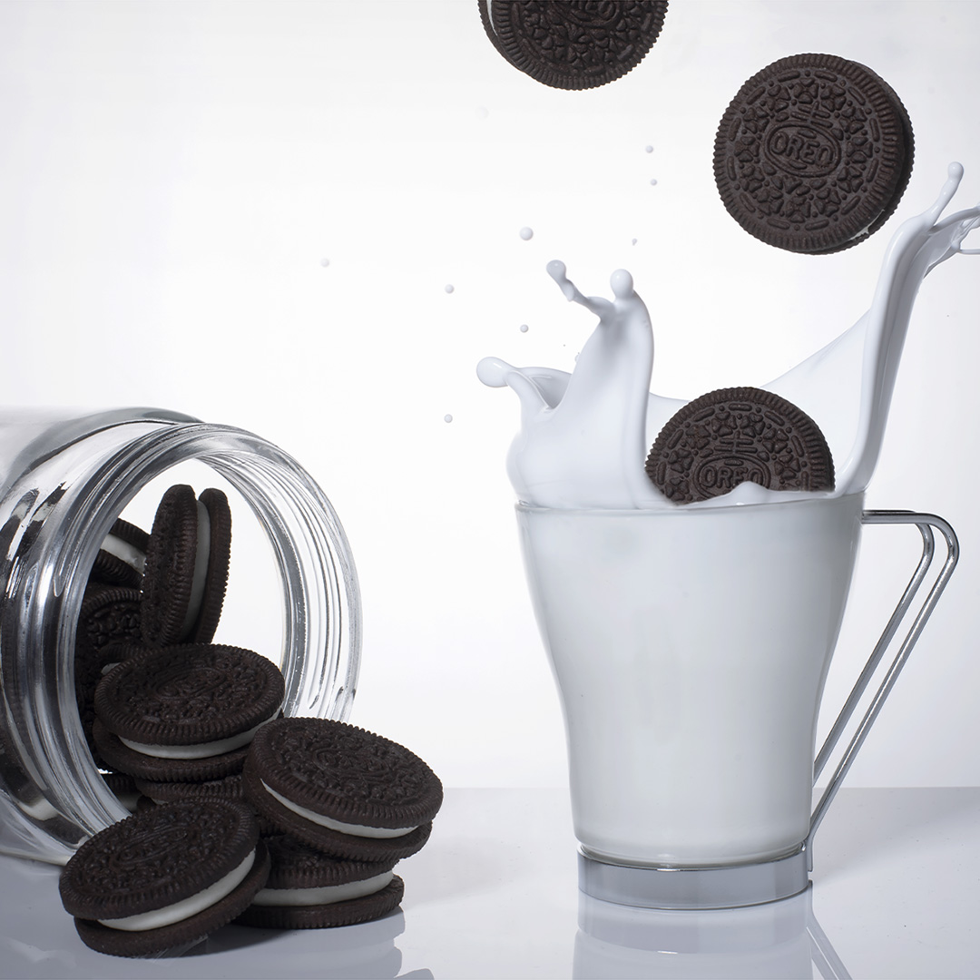 Oreo cookies splashing into milk in a cup with a small pile of Oreo cookies spilled out of a jar next to the cup