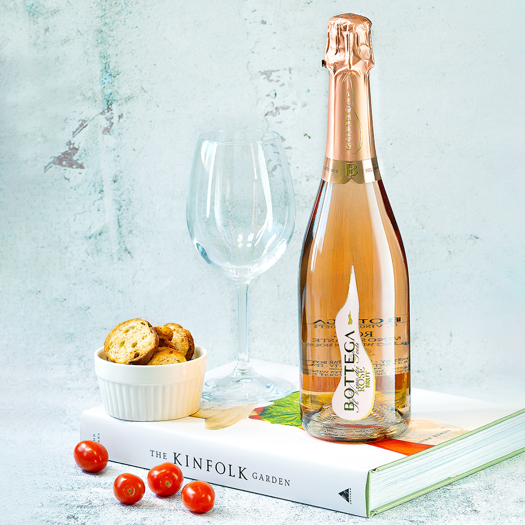 A rose bottle of sparkling wine sitting on a closed cook book, beside an empty wine glass and a dish of crackers. There are four mini tomatoes scattered in front