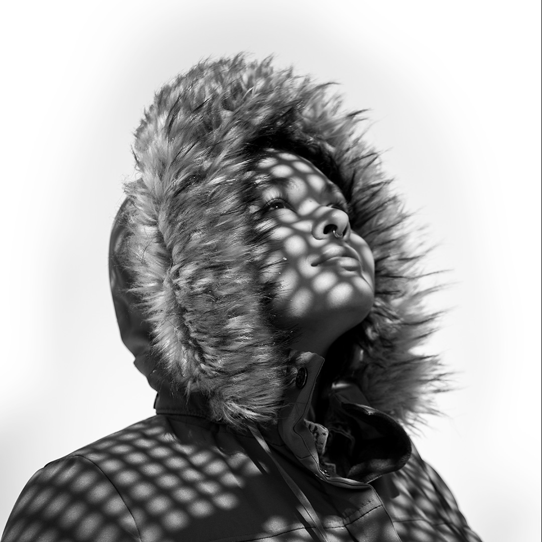 Half length black and white portrait of a young woman wearing a parka coat with hood up looking upwards and off to the side. Shadows from a lattice fence are cast over her face and jacket