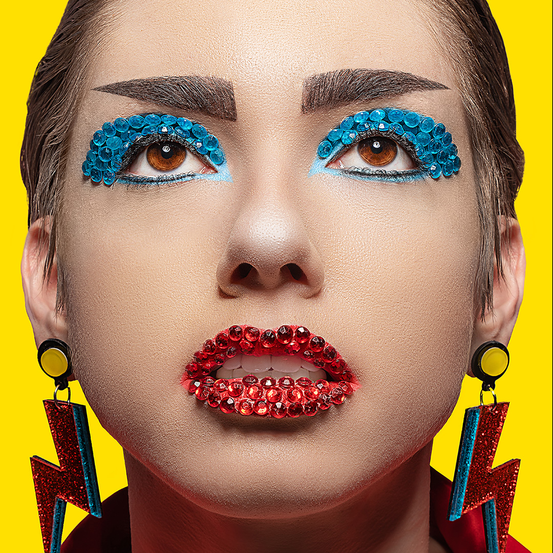 Close up head shot of a young woman with blue and redrhinestones and glitterused as makeup on eyes and lips,with a yellow backdrop.