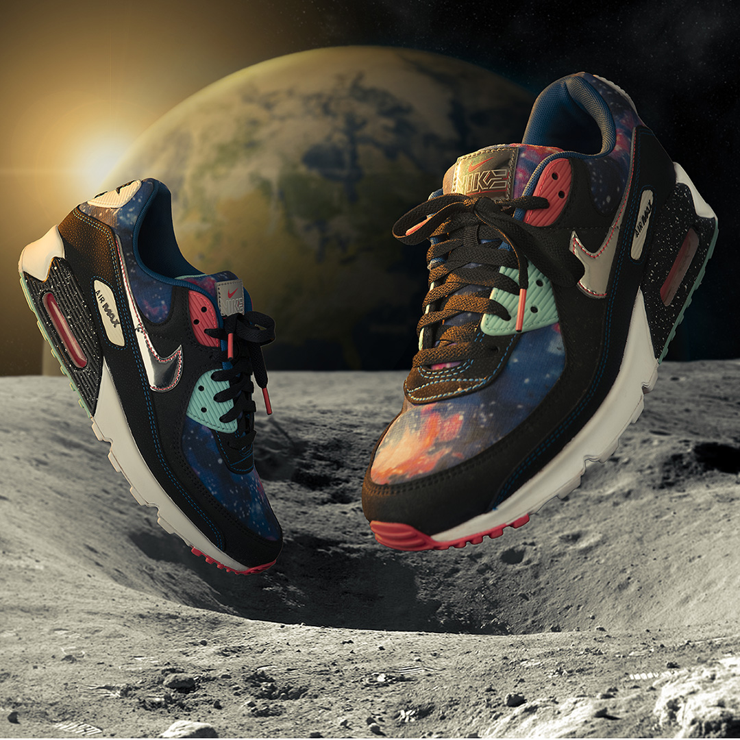 Side view of a pair of Nike running shoes with toes facing each other photographed on a Moon surface, with planet Earth in the background