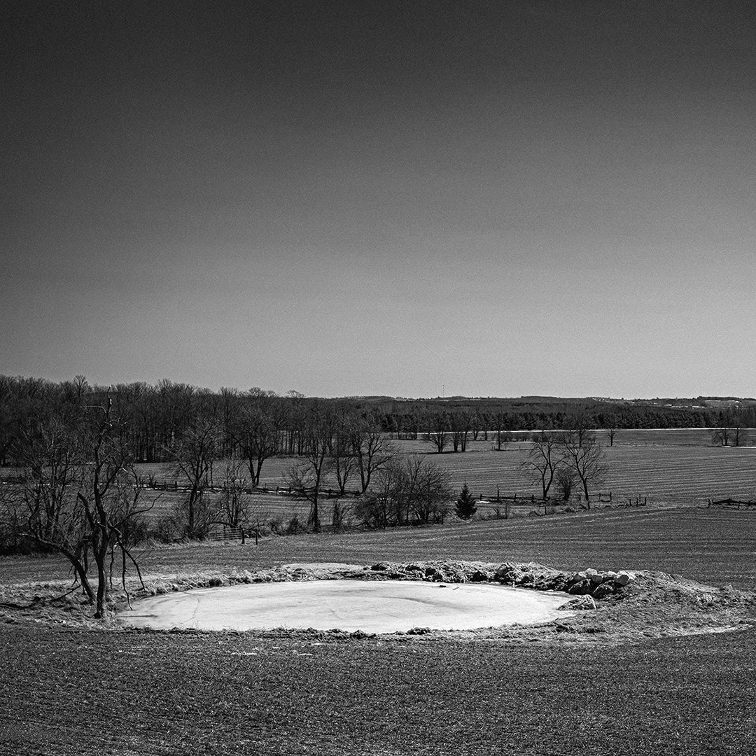 A high contrast black-and-white landscape view with a circular frozen-over pond in the foreground, with bare trees leading back into the distance.