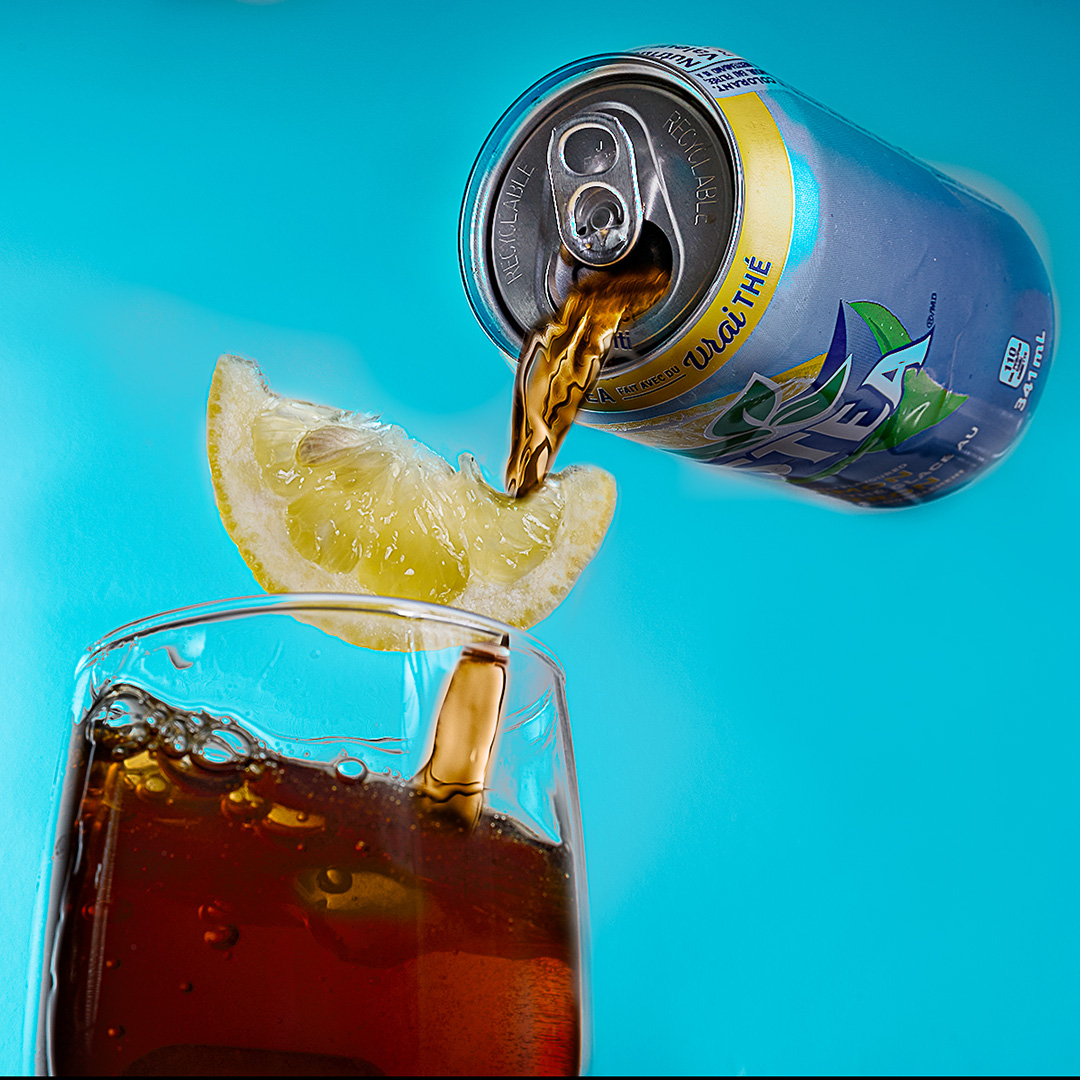 image is a can of Nestea pouring liquid into a glass with a slice of lemon falling into the glass as well.