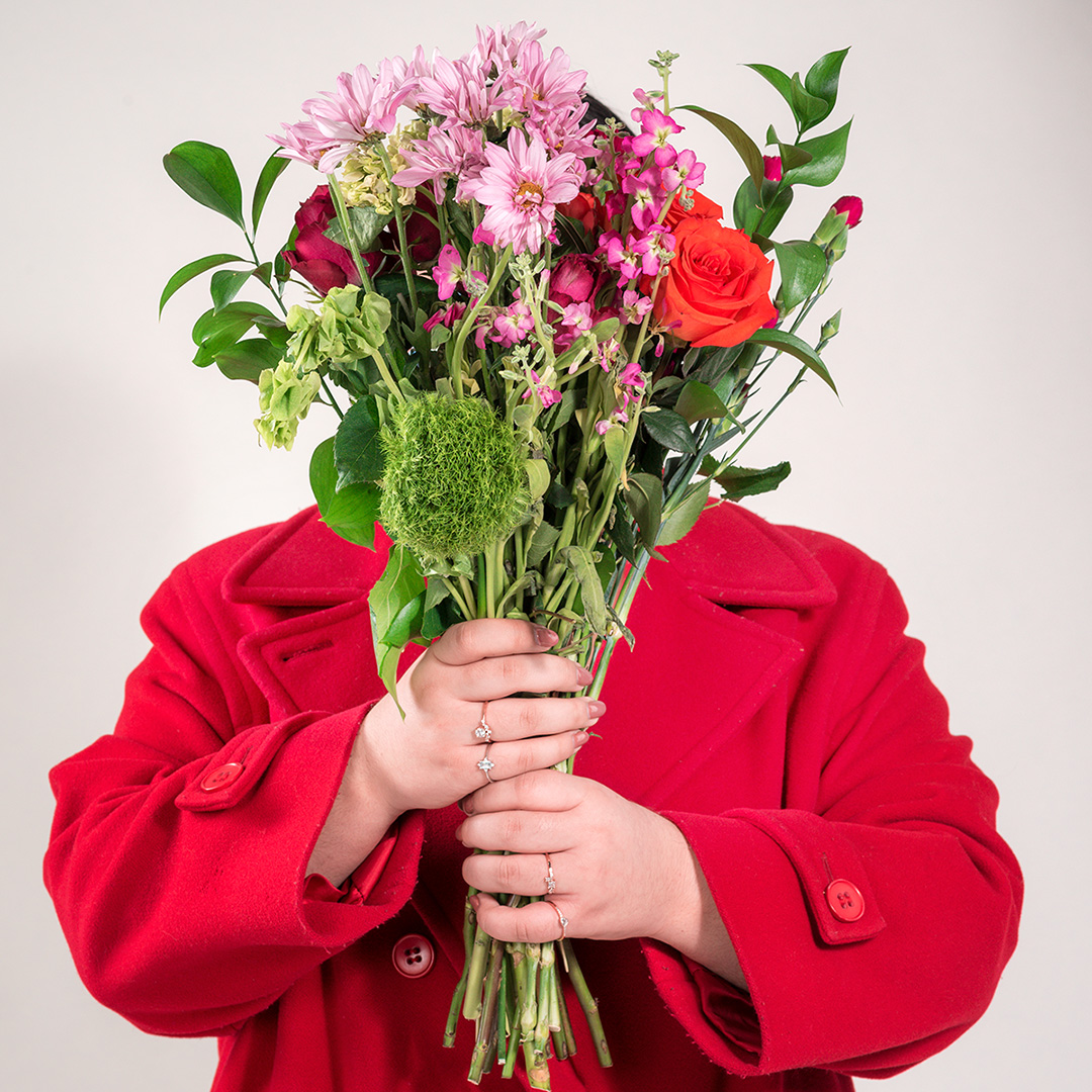 Women wearing a red jacket, holding a Bouquet of flowers in front of her face