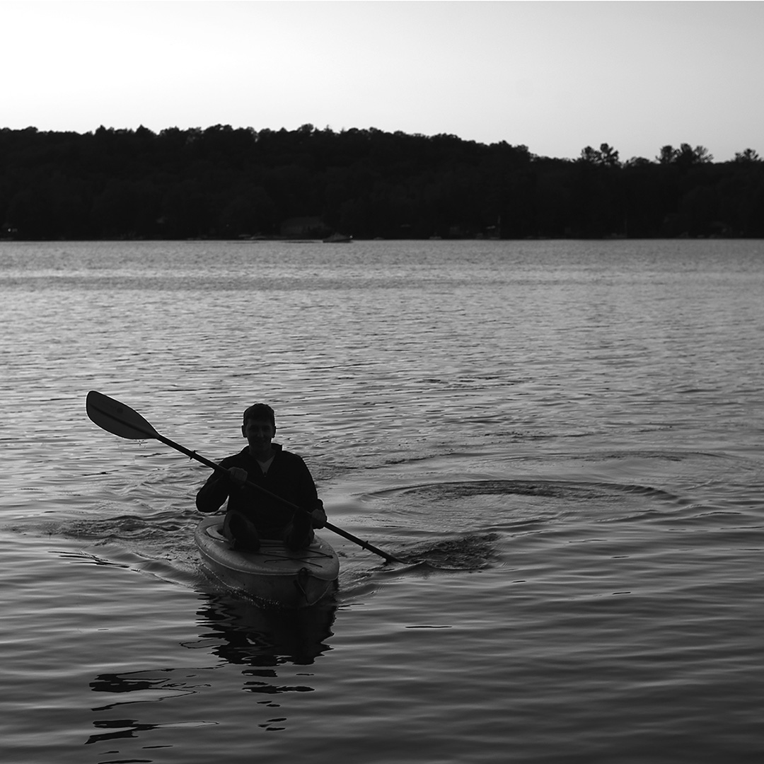 A lake view with silhouette of a person in kayak with paddle at dusk