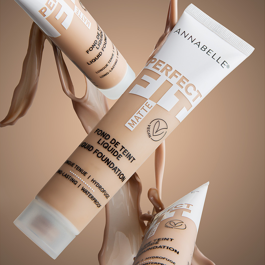 Three beige and white make up foundation bottles appear to be falling through the air, with liquid beige make up pouring around them