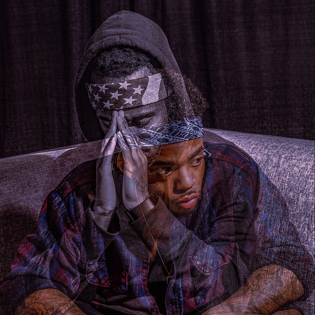 A double exposure portrait of a man sitting on a sofa, one image he looks off to the side, the other he is praying looking down