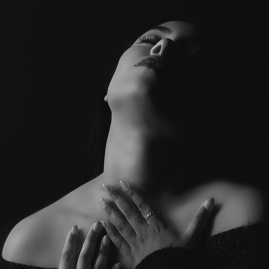 black and white image of a woman wearing a knitted sweater in a dark room with dim lighting, both her hands are softly touching her check and neck