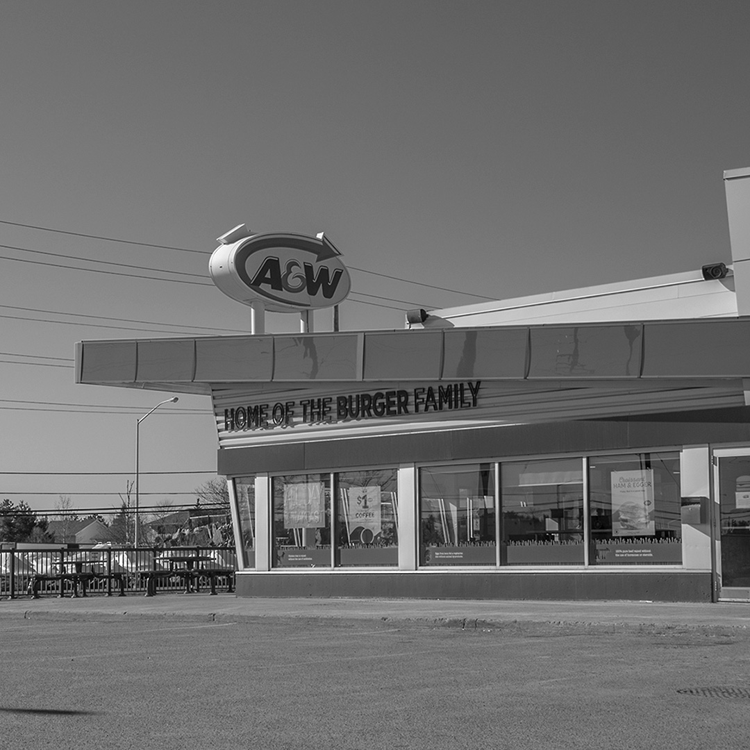 Black and white photo of an A&W restaurant showing the curve of the roof and the sign out front