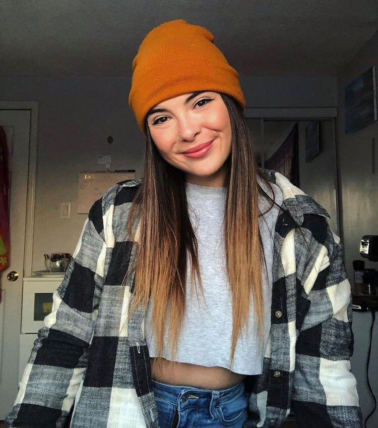 Young woman in plaid shirt and orange beanie hat